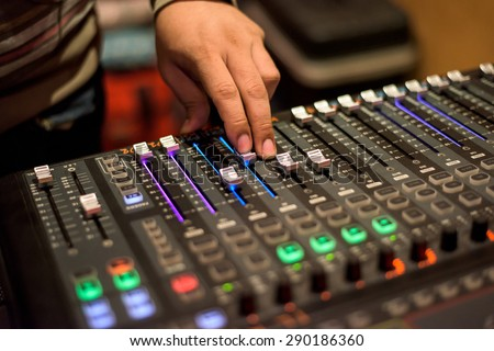 Audio mixer mixing board fader and knobs, Music mixing console with backlit buttons - stock photo