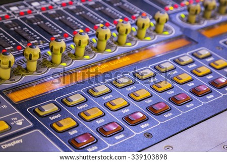 Audio mixer mixing board fader and knobs, Music mixing console with backlit buttons. Focus on detail, selective focus.