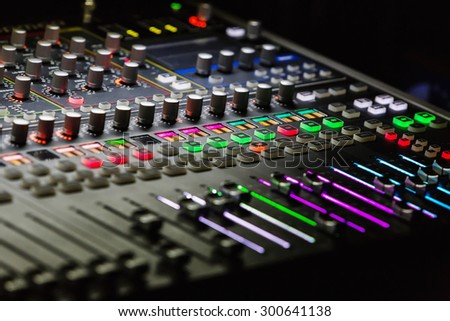 Audio mixer mixing board fader and knobs with selective focus on central buttons, Music mixing console with backlit buttons - stock photo