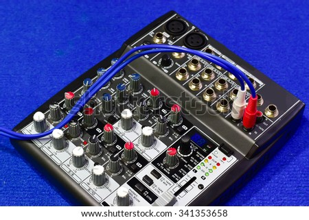 Audio mixing console on blue background. - stock photo