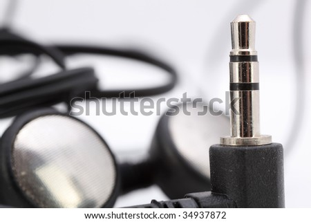 audio stereo jack with ear phones in background
