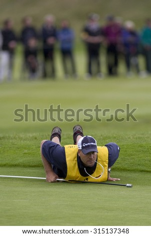Aug 30 2009; Gleneagles Scotland; Jesse Johansson caddie for Peter Hedblom (SWE) lines up the winning putt in the final round of the European Tour Johnnie Walker Championship. - stock photo