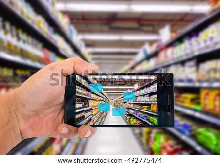Augmented reality application for retail business concept. Hand holding smart phone with A/R application on screen to scanning sale alert in supermarket. Represent A/R application in real business.