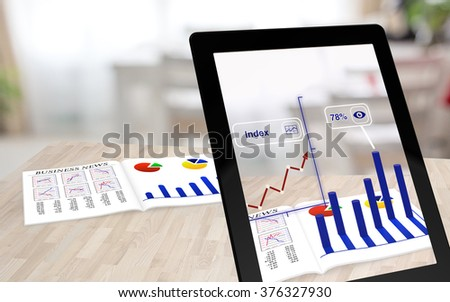 Augmented reality business magazine seen through a tablet with enhanced charts - stock photo