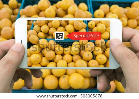 Augmented reality marketing concept. Hand holding smart phone use AR application to check sale special price of orange in retail store or fruit market mall