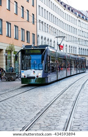 AUGSBURG, GERMANY - MAY 04, 2016: An electric tram passing by the Downtown Hall an the Isator platz square.