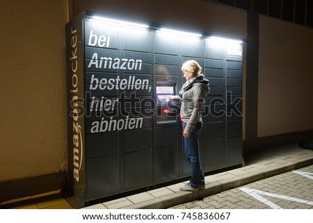 Augsburg, Germany - October 31, 2017: A woman is using an Amazon Locker station located next to an Aldi supermarket to pick up her Amazon orders even after the closing hours of the store.