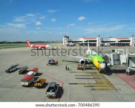 August 22, 2017 Don Mueng International Airport, Thailand : Ground staff are working at the area of the airplane of Nok Air and many trucks are parking with Air Asia in the background.