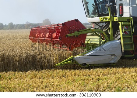 August 13, 2015, Germany near the town Dassow: part of a combine harvester working on a wheat field, agricultural scene in a rural area - stock photo