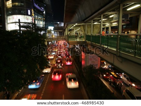August 13, 2016.  Night scene of the skywalk of Ashok BTS station with the link to Terminal 21, a trendy shopping complex in central Bangkok, while cars jammed on both sides of the road underneath.