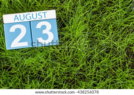 August 23rd. Image of august 23 wooden color calendar on green grass lawn background with soccer ball. Summer day. Empty space for text