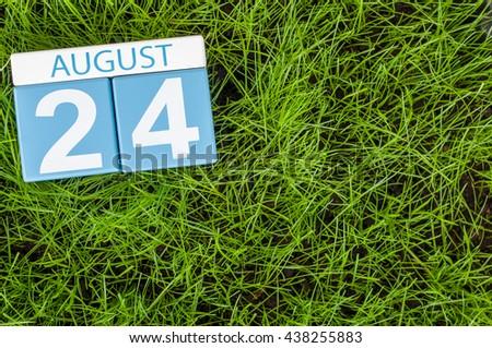 August 24th. Image of august 24 wooden color calendar on green grass lawn background with soccer ball. Summer day. Empty space for text