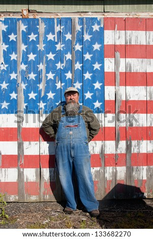 AUGUSTA - JUNE 10: Elderly man poses in front of US flag painted on wooden wall on June 10, 2012 near Augusta, Maine