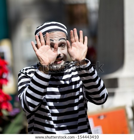 AURILLAC, FRANCE - AUGUST 21: a clown shows his handcuffed hands as part of the Aurillac International Street Theater Festival, Company Les hommes papillon,on august 21, 2013, in Aurillac,France  - stock photo
