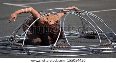 AURILLAC, FRANCE - AUGUST 22: a dancer is kneeling inside a metallic structure as part of the Aurillac International Street Theater Festival, Company Eclektic,on august 22, 2013, in Aurillac,France  - stock photo