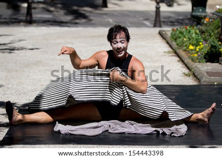 AURILLAC, FRANCE - AUGUST 21:  a funny actor plays in the street  as part of the Aurillac International Street Theater Festival, Company Les hommes papillon,on august 21, 2013, in Aurillac,France  - stock photo