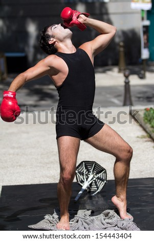 AURILLAC, FRANCE - AUGUST 21:  A funny boxer wears red boxing gloves as part of the Aurillac International Street Theater Festival, Company Les hommes papillon,on august 21, 2013, in Aurillac,France  - stock photo