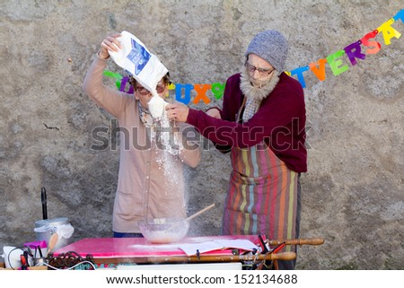 AURILLAC, FRANCE - AUGUST 21: a funny elderly couple is making a cake as part of the Aurillac International Street Theater Festival, Company L'arbre a vache ,on august 21, 2013, in Aurillac,France. - stock photo