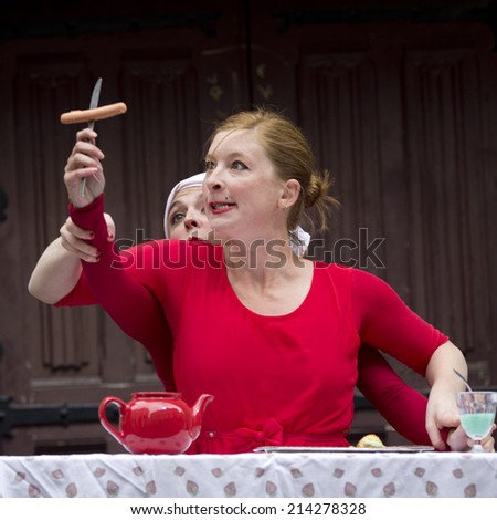 AURILLAC, FRANCE-AUGUST 20: a funny woman looks at a sausage on a fork as part of the  Aurillac International Street Theater Festival, cie Lily Kamikaz,on august 20, 2014, in Aurillac,France.  - stock photo