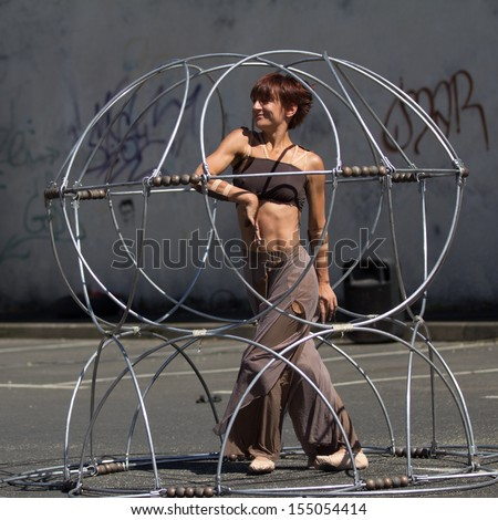AURILLAC, FRANCE - AUGUST 22: a prisoner moves inside a metallic structure as part of the Aurillac International Street Theater Festival, Company Eclektic,on august 22, 2013, in Aurillac,France  - stock photo