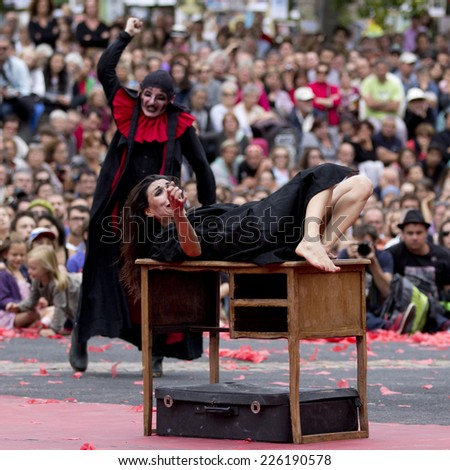 AURILLAC, FRANCE-AUGUST 22: a scared woman is attacked by a man as part of the Aurillac International Street Theater Festival, cie teatro del silencio there august 22, 2014 in Aurillac, France. - stock photo