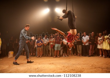 AURILLAC, FRANCE - AUGUST 22: a trapeze artist moves in the middle of a big top as part of the Aurillac International Street Theater Festival, Company Off ,on august 22, 2012, in Aurillac,France. - stock photo