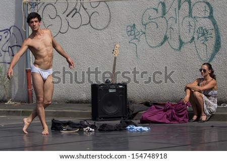 AURILLAC, FRANCE - AUGUST 22:  a woman looks at a semi-naked dancer as part of the Aurillac International Street Theater Festival, Company Monsieur Linea,on august 22, 2013, in Aurillac,France  - stock photo