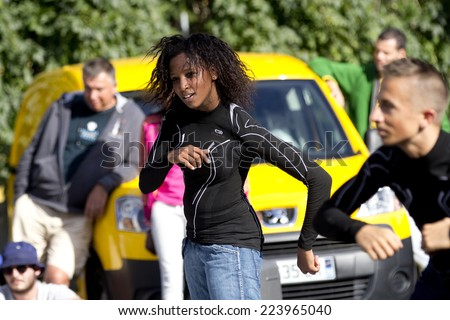 AURILLAC, FRANCE-AUGUST 25: a young woman dances hip hop in the street as part of the Aurillac International Street Theater Festival, cie Bakhus 24,on august 25, 2014, in Aurillac,France.  - stock photo