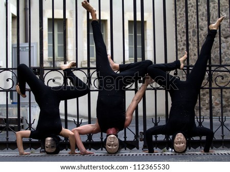 AURILLAC, FRANCE - AUGUST 23: actors upside down in the street as part of the Aurillac International Street Theater Festival, show La diagonale du Fou, on august 23, 2012, in Aurillac,France. - stock photo