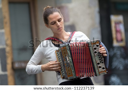 AURILLAC, FRANCE - AUGUST 24: an accordion player in the street as part of the Aurillac International Street Theater Festival, show by Die Kurbe, on august 24, 2012, in Aurillac,France.