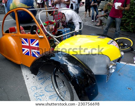 AURILLAC, FRANCE, AUGUST 21: An artist has built a fake 2cv for his show as part of the Aurillac international Street Theater Festival, on august 21, 2014 in Aurillac, France. - stock photo