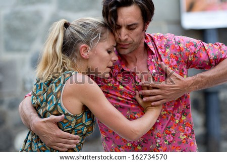 AURILLAC, FRANCE - AUGUST 23: An embracing couple dances tango, as part of the Aurillac International Street Theater Festival, cie Moebius, on august 23, 2013, in Aurillac,France  - stock photo