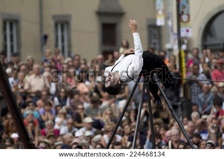 AURILLAC, FRANCE-AUGUST 22: balancing act in front of a big crowd as part of the Aurillac International Street Theater Festival, cie teatro del silencio ,on august 22, 2014, in Aurillac,France.  - stock photo