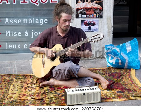 AURILLAC, FRANCE, AUGUST 21: Barefoot and hairy musician playing the guitar in the street as part of the Aurillac international Street Theater Festival, on august 21, 2014 in Aurillac, France. - stock photo