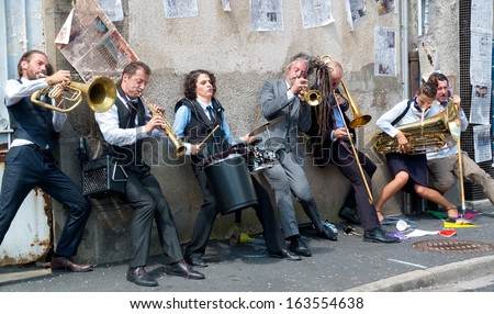 AURILLAC, FRANCE - AUGUST 23: Group of musicians playing against a wall, as part of the Aurillac International Street Theater Festival, cie Rhinofanpharyngite,on august 23, 2013, in Aurillac,France  - stock photo
