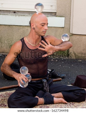 AURILLAC, FRANCE - AUGUST 23: Portrait of a skillful artist, named Jyoti, playing with balls as part of the Aurillac International Street Theater Festival, on august 23, 2013, in Aurillac,France  - stock photo