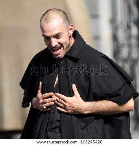 AURILLAC, FRANCE - AUGUST 21: Portrait of an actor wearing black clothes, as part of the Aurillac International Street Theater Festival, cie Theatre du Vertige,on august 21, 2013, in Aurillac,France  - stock photo