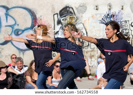 AURILLAC, FRANCE - AUGUST 22: Three dancers wearing funny hairstyles, as part of the Aurillac International Street Theater Festival, cie Groupe Berthe, on august 22, 2013, in Aurillac,France  - stock photo