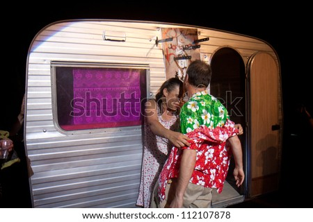 AURILLAC, FRANCE - AUGUST 22: Two actors play near a caravan as part of the Aurillac International Street Theater Festival,show by the Company Off ,on august 22, 2012, in Aurillac,France. - stock photo