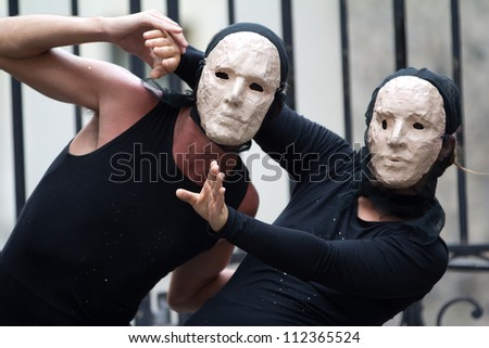 AURILLAC, FRANCE - AUGUST 23: two actors wearing a white mask as part of the Aurillac International Street Theater Festival, show La diagonale du Fou, on august 23, 2012, in Aurillac,France. - stock photo