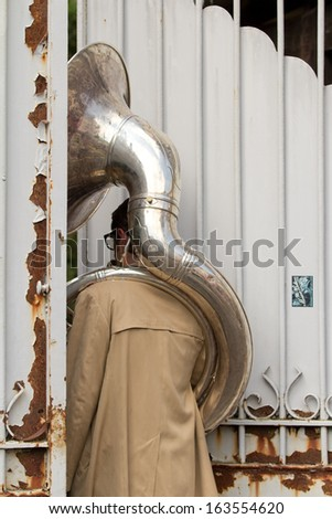 AURILLAC, FRANCE - AUGUST 23: Unusual situation for a tuba player, as part of the Aurillac International Street Theater Festival, cie Rhinofanpharyngite,on august 23, 2013, in Aurillac,France  - stock photo