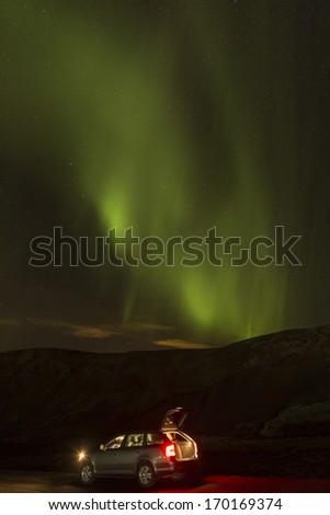 Aurora above car & hill - stock photo