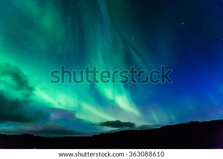 Aurora at night over the land as a background - stock photo