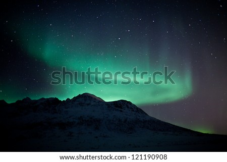 Aurora Borealis in arctic skies behind mountains in Norway - stock photo