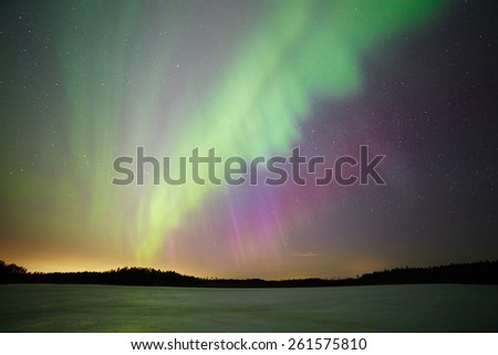 Aurora borealis or northern lights photographed from straight below. Vibrant colors of the corona and starry sky on the background. - stock photo