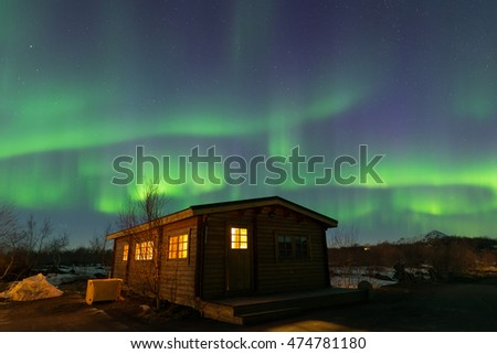 Aurora borealis over a wooden house in Iceland