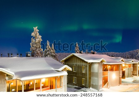 Aurora borealis over village of cabins at north part of Finland