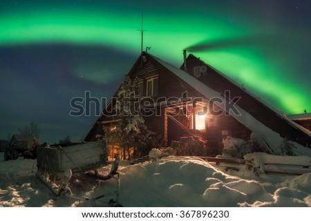 Aurora over the wooden house. Northern lights in the Khibiny, Russia, Murmansk, lake Lovozero. - stock photo