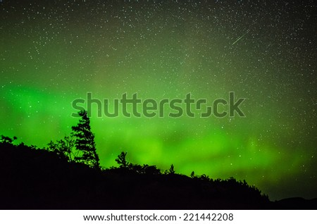 Aurora with meteor streaking above - stock photo