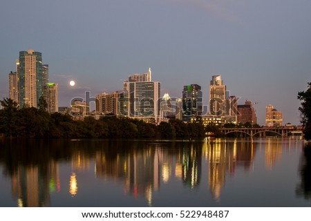 Austin skyline reflection off Lady Bird Lake on supermoon evening viewed from Zilker Park trail.